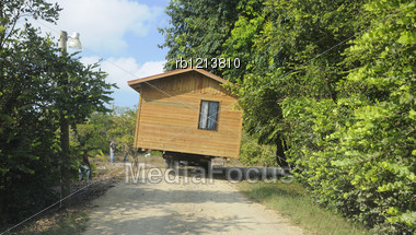 Wooden House Being Transported Along A Narrow Road Stock Photo