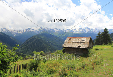 Wooden House In Mountains On Blue Clody Sky Background Stock Photo