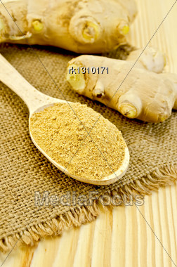 Wooden Spoon With The Powder Of Ginger, Ginger Root On A Napkin On A Burlap Background Wooden Board Stock Photo