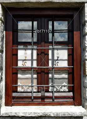 Wooden Window With Elegant Curtains, Sky Reflection And Steel Bars On The Stone House Stock Photo