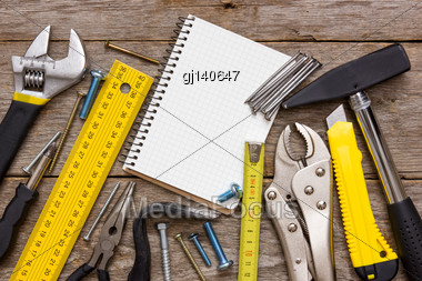 Work Tools And Notebook On The Wooden Background Stock Photo