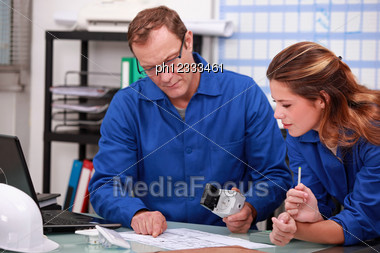 Worker And Intern Checking Stock Levels Stock Photo
