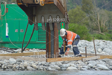 Worker Checks The Position Of A Pile In A Bridge Construction Project Stock Photo