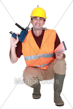 Worker Kneeling With Drill Stock Photo