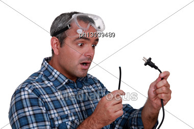 Worker Looking At A Cut Electrical Wire Stock Photo