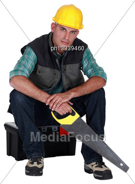 Workers Sitting On Toolbox With Saw In Hand Stock Photo