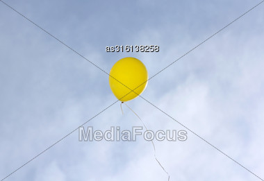 Yellow Balloon Flying On A Blue Sky Background Stock Photo