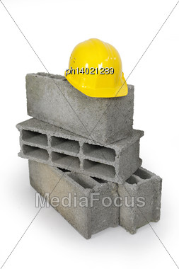 Yellow Hard Hat Resting On Pile Of Breeze Blocks Stock Photo
