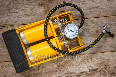 Yellow Inflator With Gauge On Wooden Background Stock Photo