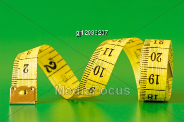 Yellow Measure Tape,isolated On Green Background Stock Photo