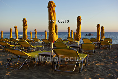 Yellow Sunshades And Sunbeds At Sandy Beach At Summer Sundown With Blue Sea And Sky In Background Stock Photo