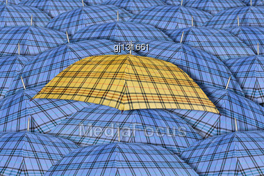 Yellow Umbrella Standing Out From Background Of Blue Umbrellas Stock Photo