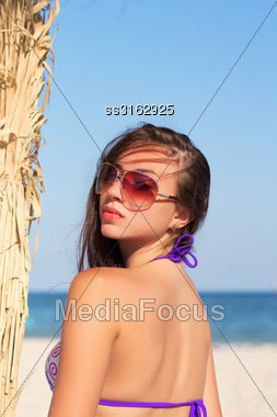 Young Alluring Woman In Sunglasses Posing On The Beach Stock Photo