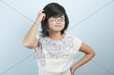 Young Asian Woman Scratching Her Head While In Thought Stock Photo