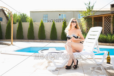 Young Attractive Blond Woman Posing With A Drink Near The Pool Outdoors Stock Photo