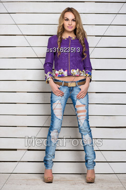 Young Attractive Blond Woman In Ripped Jeans And Purple Jacket Posing Near The White Wooden Wall Stock Photo