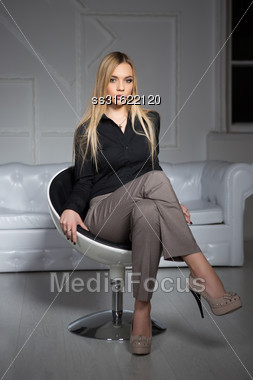 Young Attractive Blond Woman Wearing Business Clothes Sitting On A Chair Stock Photo