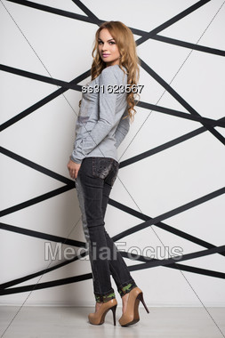 Young Attractive Blond Woman Wearing Gray Blouse And Jeans Stock Photo