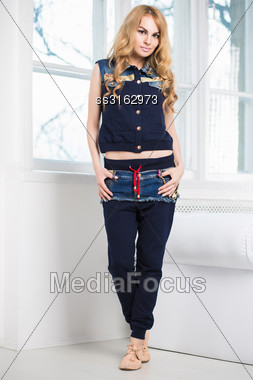 Young Attractive Blonde Posing In Blue Vest And Pants Near The Window Stock Photo