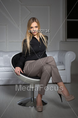 Young Attractive Blonde Wearing Business Clothes Sitting On A Chair Stock Photo