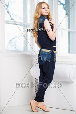 Young Attractive Woman Posing In Blue Vest And Pants Near The Window Stock Photo
