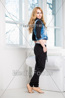 Young Attractive Woman Posing In Fashionable Clothes Near The Window Stock Photo