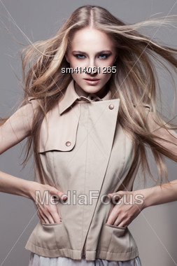 Young Beautiful Blond Woman With Flying Hair Wearing Fashionable Waistcoat Stock Photo