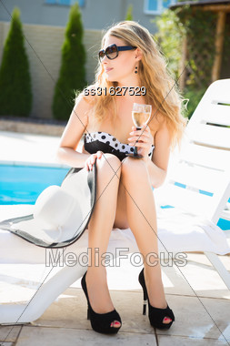 Young Beautiful Blond Woman In Swimming Suit Posing With A Drink Near The Pool Stock Photo