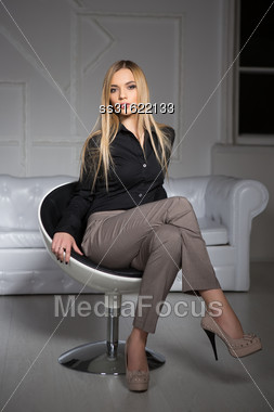 Young Beautiful Blonde Wearing Business Clothes Sitting On A Chair Stock Photo