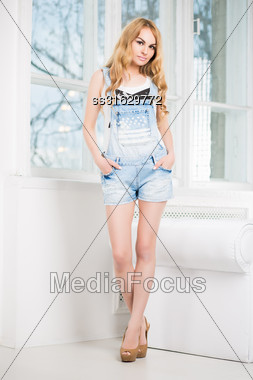 Young Beautiful Woman Posing In Short Denim Overalls Near The Window Stock Photo