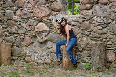 Young Beautiful Woman Sitting On The Log Near Old Castle Ruins Stock Photo