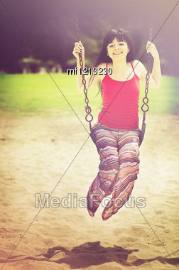 Young Beautiful Woman On Swing In Summer Sunny Day Stock Photo