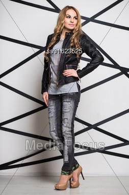 Young Beautiful Woman Wearing Leather Jacket And Gray Jeans Stock Photo