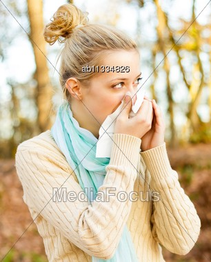 Young Beautiful Women Suffering From Influenza, Blowing Her Nose Stock Photo