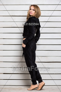Young Blond Woman In Black Clothes Posing Near White Wall Stock Photo
