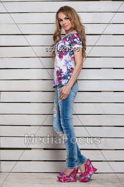 Young Blond Woman Posing In Blue Ripped Jeans And White Flowered T-shirt Stock Photo