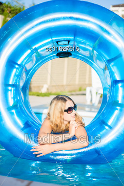 Young Blond Woman Posing With Rubber Ring In Swimming Pool Stock Photo