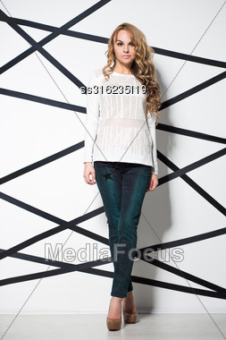 Young Blond Woman Wearing Jeans And White Blouse Posing In The Studio Stock Photo