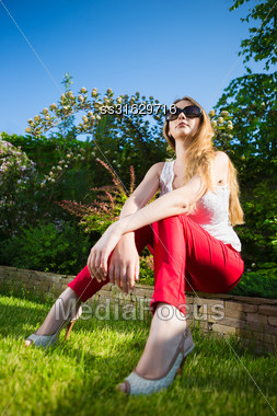 Young Blond Woman Wearing White Top And Red Panties Sitting On The Stone Fence Outdoors Stock Photo