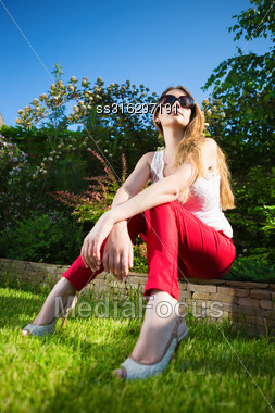 Young Blond Woman Wearing White Top And Red Panties Sitting On The Stone Fence Stock Photo