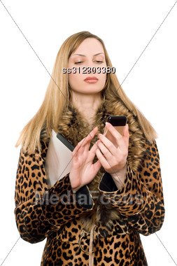 Young Blonde In The Fur Coat Calling Stock Photo
