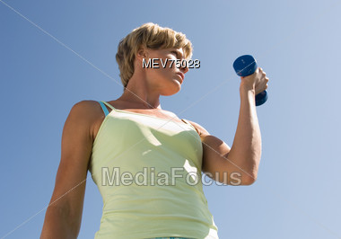 Young Blonde Woman Exercising with Weights Stock Photo