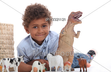 Young Boy Playing With A Toy Dinosaur And Collection Of Domestic Animals Stock Photo
