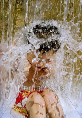 Young Boy Under Waterfall Stock Photo