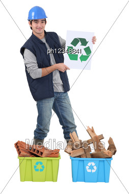 Young Bricklayer Holding Recycling Logo Stock Photo