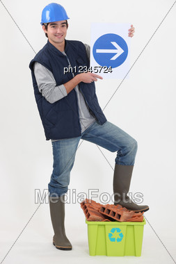 Young Bricklayer In Studio Holding Sign With Arrow Stock Photo