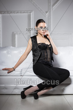 Young Brunette In Black Clothes Posing On White Sofa Stock Photo