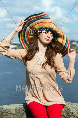 Young Brunette In Colorful Hat Sitting On A Rock By The River With Closed Eyes Stock Photo
