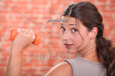 Young Brunette Lifting Dumbbell Stock Photo