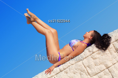 Young Brunette Lying On The White Stone Wall Stock Photo
